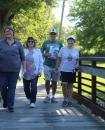 COMMERCIAL-NEWS | ROBERT TOMLINSON - (From left to right) Brittany Wenzel, Rachelle Roberts, Arlan Wenzel and Lynn Wenzel walk across one of the bridges at Scidmore Park during Monday's 11th annual Three Rivers Woman's Club Historic Labor Day Bridge Walk.