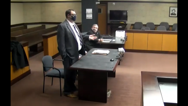 Screenshot via YouTube/Zoom - Former St. Joseph County Prosecutor John McDonough (standing) speaks to Kalamazoo County District Court Judge Vincent Westra (not pictured) during a plea hearing in his drunk driving case Thursday. McDonough pled guilty to operating while visibly impaired in his case, stemming from a drunk driving incident in Lockport Township in May 2020.