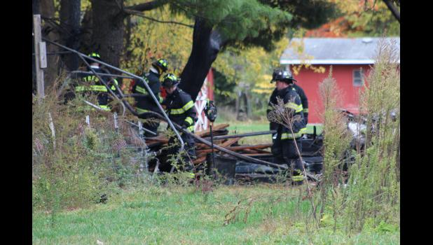 COMMERCIAL-NEWS | ROBERT TOMLINSON - Three Rivers Fire Department firefighters review what remains of an RV fire that occurred Friday behind a home in the 16000 block of Lover's Lane in Three Rivers. A 40-year-old man was arrested for arson in connection with the fire.