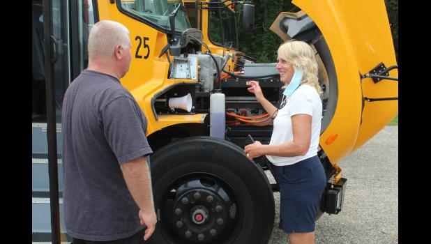COMMERCIAL-NEWS | ROBERT TOMLINSON - State Sen. Kim LaSata (right) looks at one of the electric school buses in the Three Rivers Community Schools fleet during a visit to the district Monday. During the visit, TRCS Fleet Supervisor Ron Yoder (left) showed LaSata the differences between the electric bus and a regular diesel bus.