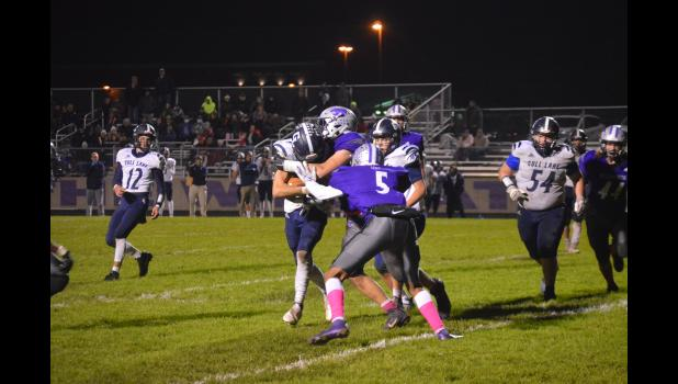 Commercial-News | Scott Hassinger - Three Rivers' defenders Lloyd Ruesink and Angelo Hausmanis (5) combine to tackle Gull Lake ballcarrier Ben Jackson.