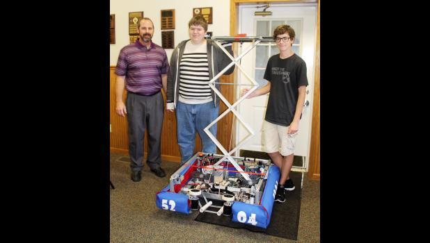 Robocats - Following their presentation to the Three Rivers Rotary Club Thursday, Oct. 14, Robocats advisor Phil Webb, three-year member Brandon Bottles and two-year member Hunter Schnetzler stand with their robot from last year. Commercial-News/Elena Meadows